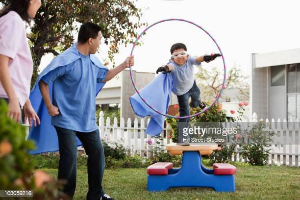 Korean boy in superhero costume jumping through hoop