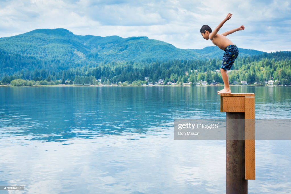 Korean boy jumping off platform into lake : Stock Photo