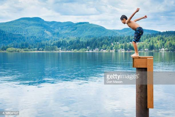 Korean boy jumping off platform into lake