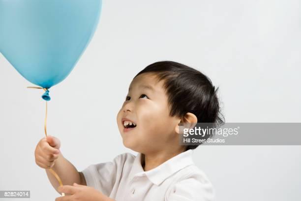 Korean boy looking at balloon