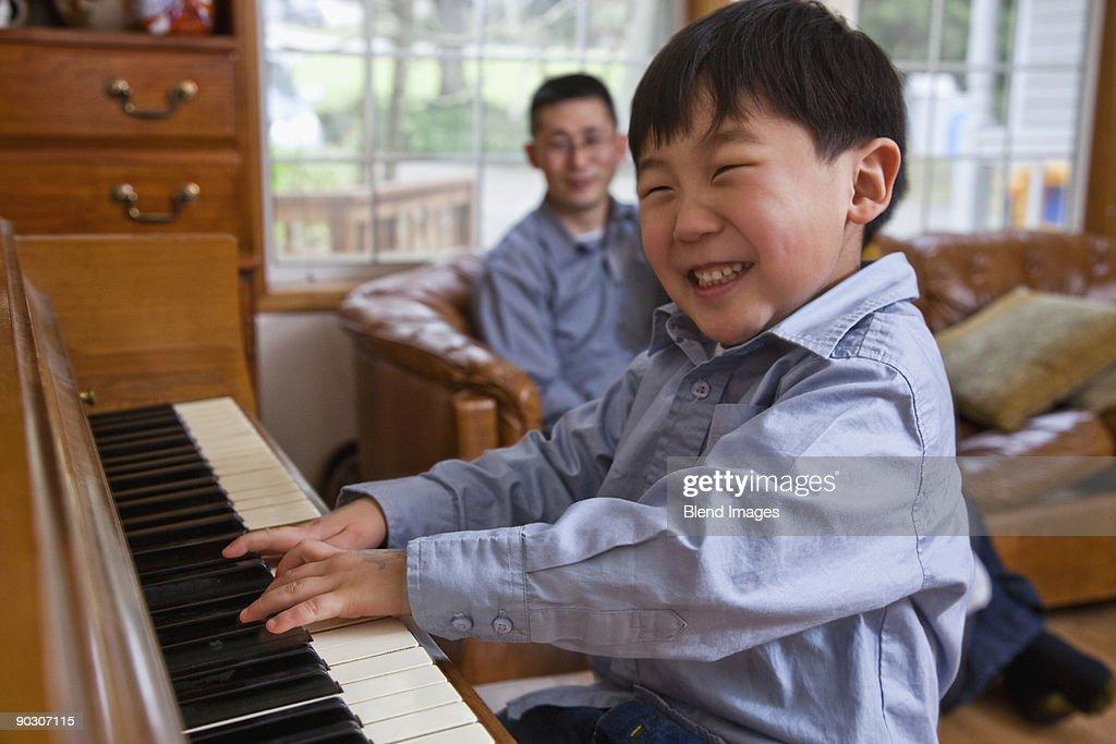 Korean boy playing piano : Stock Photo