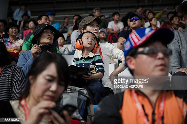 A Korean boy wears ear protection to avoid the loud sound of the car engines during the Formula One Korean Grand Prix in Yeongam on October 6 2013...