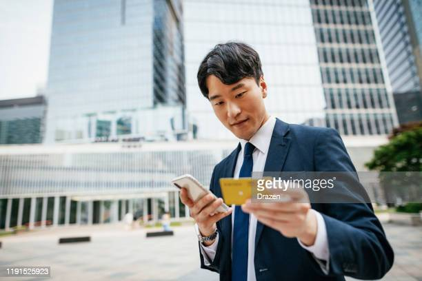 korean businessman using smart phone and credit card for online payment - korea stock pictures, royalty-free photos & images