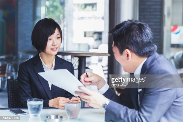 korean businesswoman meeting with her financial advisor at a cafe - formal businesswear stock pictures, royalty-free photos & images