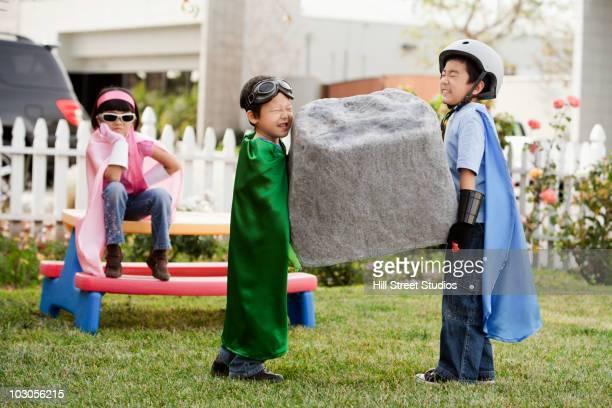 korean children as superheros carrying large boulder - oggetti pesanti foto e immagini stock