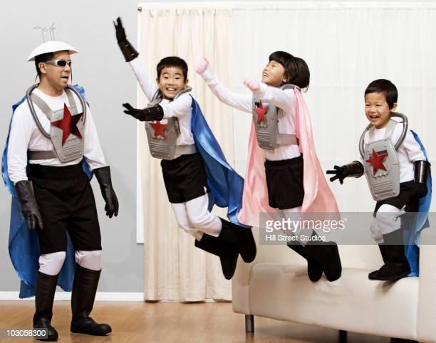 Korean children in superhero costumes jumping off sofa