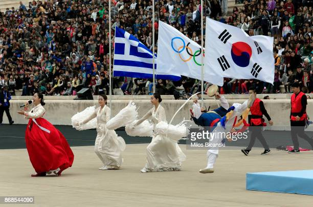 Korean dancers dressed in traditional costume perform infront of the Greek Olympic and South Korean flags during the handover ceremony of the Olympic...