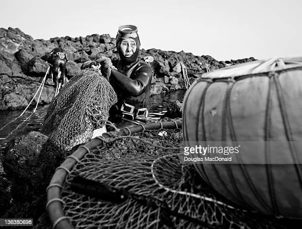 A Korean diving woman fixes her nets on southern Jeju Island South Korea