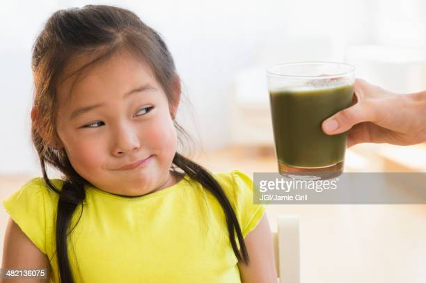 Korean girl frowning at glass of green smoothie
