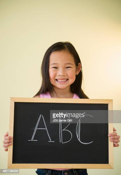 Korean girl holding chalkboard with ABC text