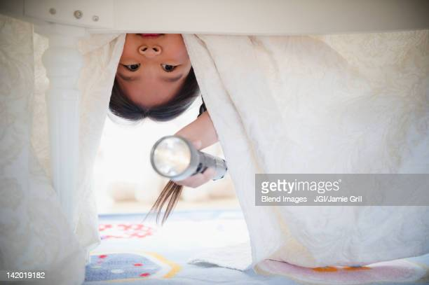 Korean girl looking under bed with flashlight