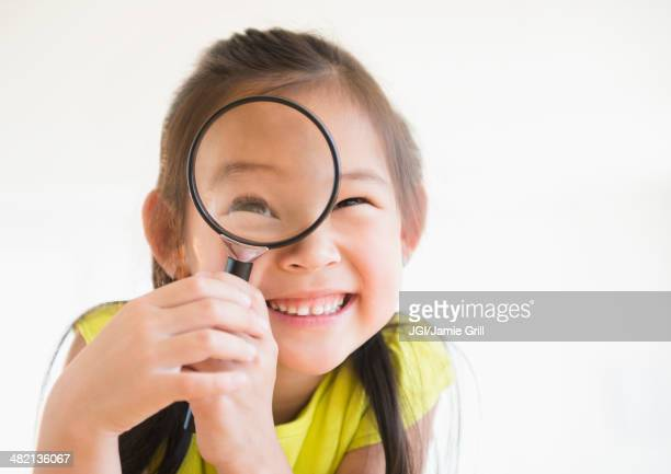 Korean girl using magnifying glass