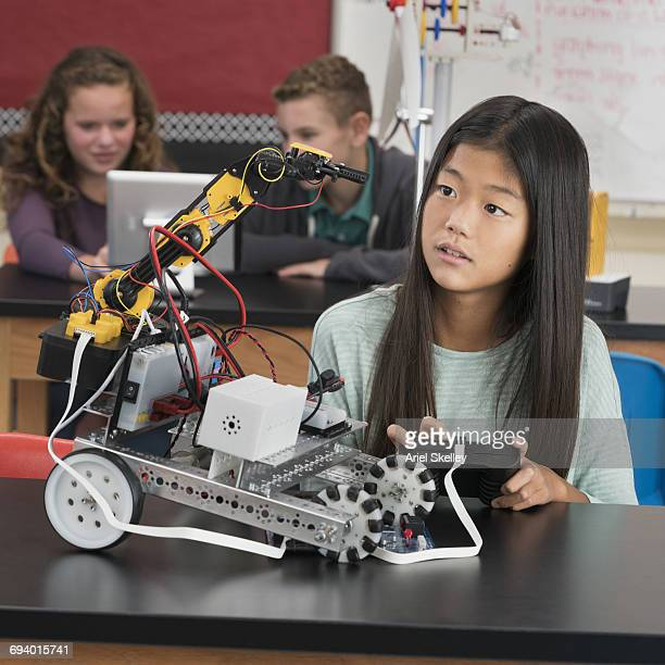 Korean girl using remote control with robot in robotics class