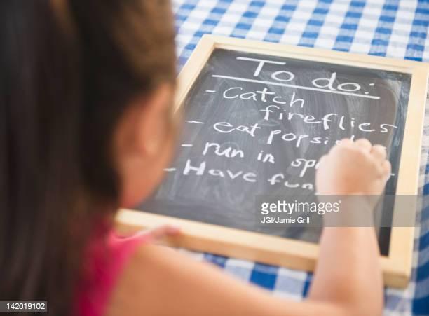 Korean girl writing to do list on blackboard