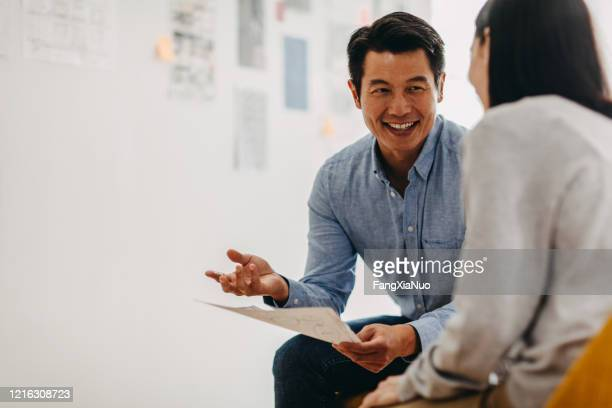 korean graphic designer sharing ideas during meeting in modern office studio - two people stock pictures, royalty-free photos & images