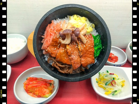 Korean grilled beef on rice served in stone bowl w/ namul garnish and kimchi appetizer, food model - gettyimageskorea