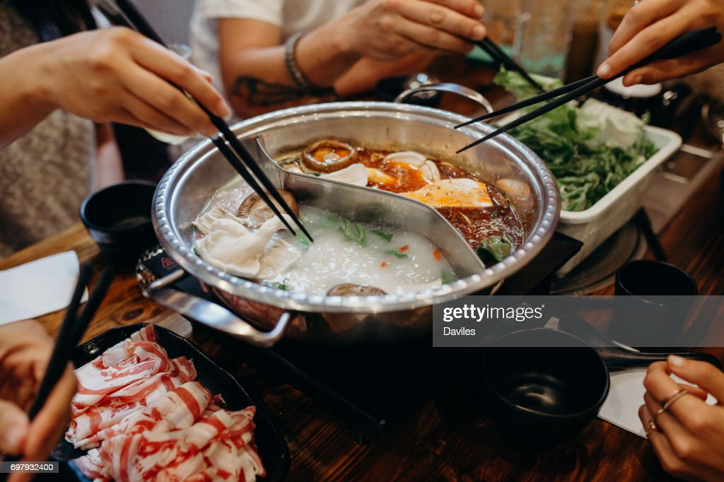 Korean hot pot meal. Hands taking food with chopsticks. : Stock Photo