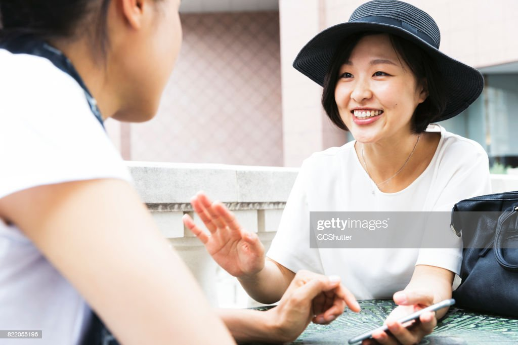 Korean lady showing her smart phone to her Japanese friend : Stock Photo