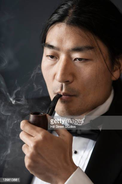 korean man in tuxedo smoking pipe - smoking stockfoto's en -beelden
