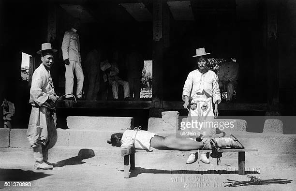 Korean man is beaten with a rod undated probably in the 1910's
