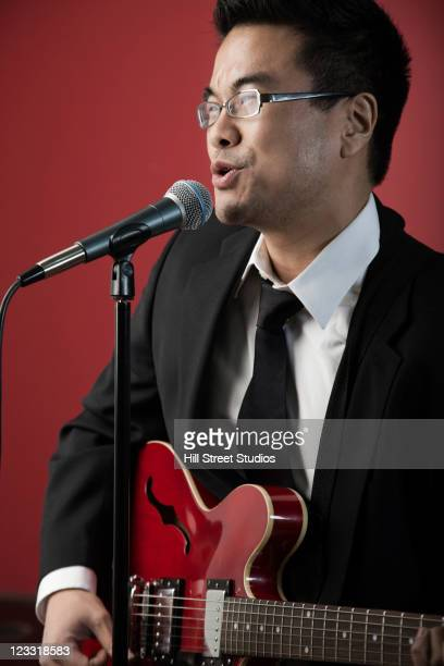 korean man playing guitar and singing into microphone - gardena california stock pictures, royalty-free photos & images