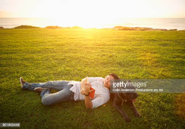 korean man reading with dog in field - one animal stock pictures, royalty-free photos & images