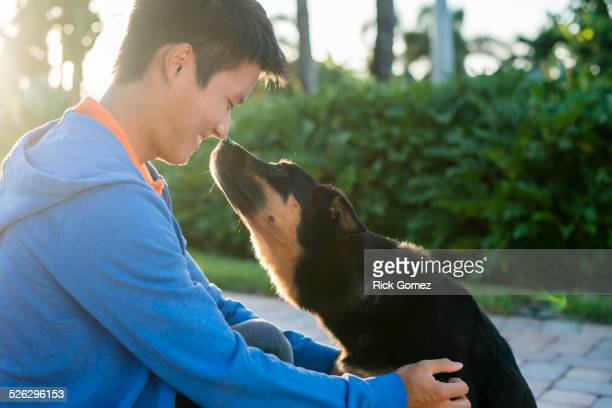 Korean man rubbing noses with dog
