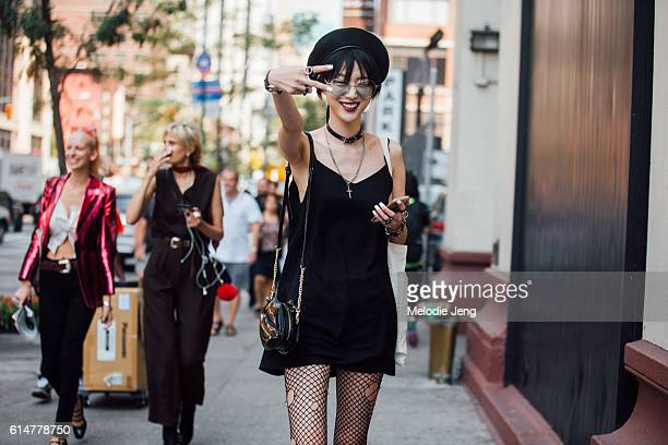Korean model Sora Choi throws a peace sign after the Creatures of the Wind show and wears an all black outfit including sailorstyle hat circularframe...