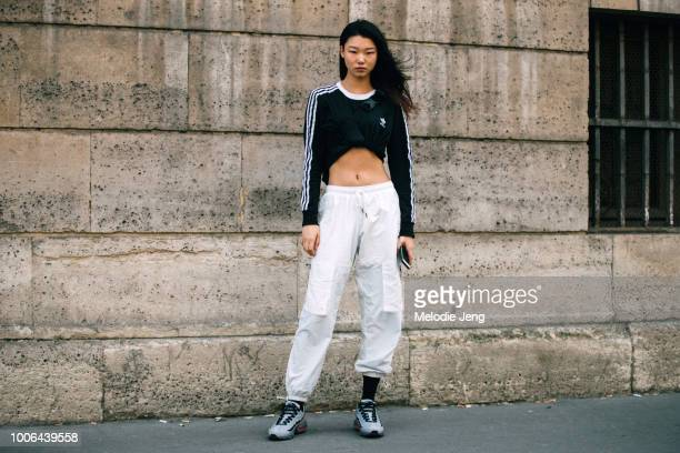 Korean model Yoon Young Bae wears a cropped Adidas black shirt white cargo pants and Nike Air Max 95 sneakers after the Y3 show during Paris Fashion...