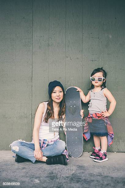 Korean mother and daughter posing with skateboard