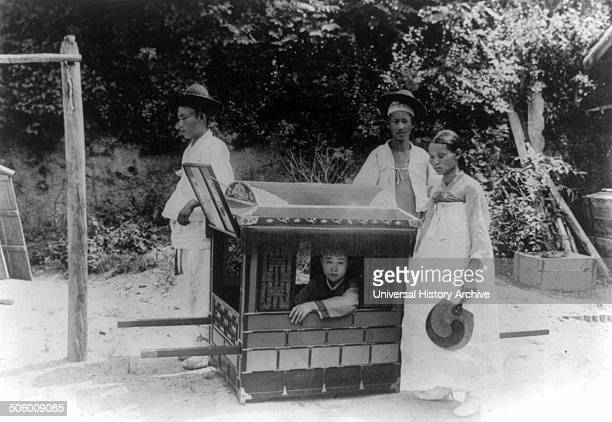 Korean noble boy carried by servants in a sedan chair 1900