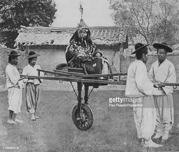 A Korean nobleman on a unicycle supported by four bearers Korea circa 1900