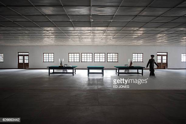 A Korean People's Army soldier walks before the tables where the Korean War armistice agreement was signed near the Demilitarized Zone separating...