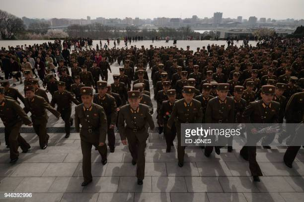 TOPSHOT Korean People's Army soldiers arrive to pay their respects before the statues of late North Korean leaders Kim Il Sung and Kim Jong Il at...