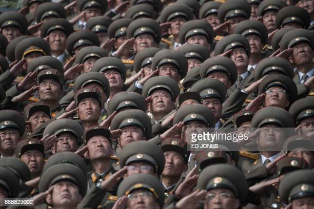 Korean People's Army soldiers salute as they watch a military parade marking the 105th anniversary of the birth of late North Korean leader Kim...