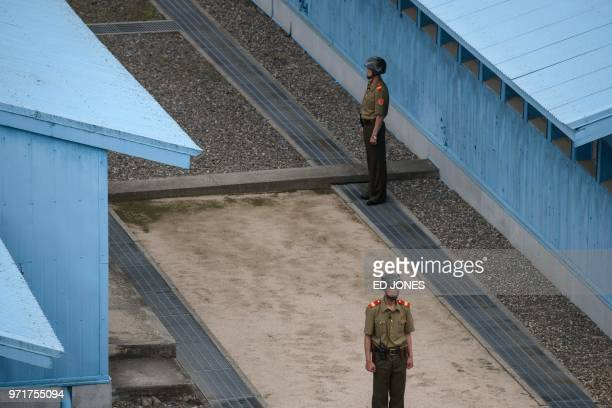 Korean People's Army soldiers stand before the Military Demarcation Line at the truce village of Panmunjom on the North Korean side of the...