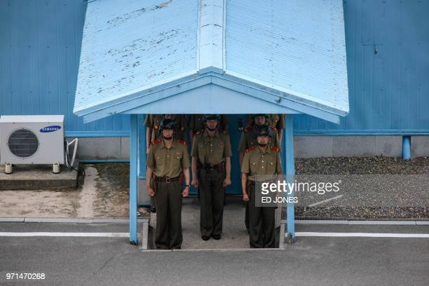 TOPSHOT Korean People's Army soldiers stand beneath the entrance to a pavillion before the Military Demarcation Line at the truce village of...