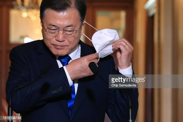 Korean President Moon Jae-in removes his face mask before delivering remarks with Speaker of the House Nancy Pelosi in her offices at the U.S....
