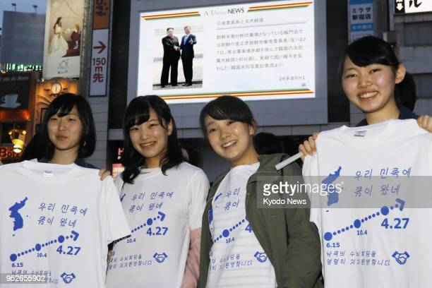 Korean residents of Japan show off T shirts bearing the phrase We earnestly support the interKorean summit in Tokyo's Shinjuku area on April 27 2018...
