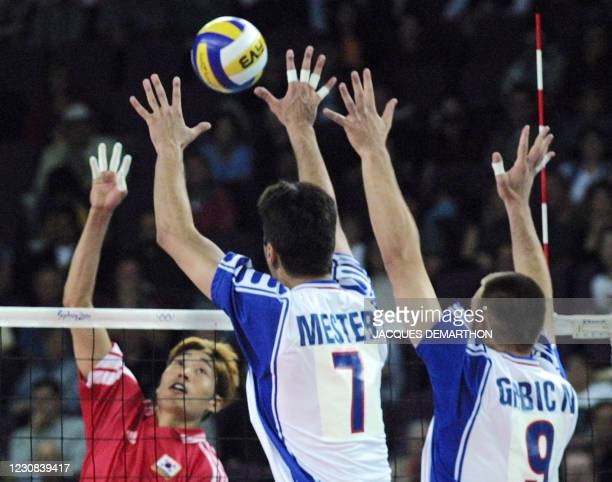Korean Shin Jin-Sik tries to smash over Yugoslavia's Djula Mester and Nikola Grbic during their men's volleyball elimination match at the XXVII...