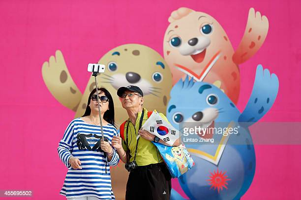 Korean spectators take a photo with the mascot before during the Opening Ceremony of the 2014 Asian Games at Incheon Asiad Stadium on September 19,...