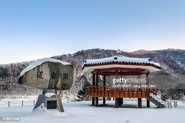 A Korean style gazebo and the name plate stone by the lake in snowy winter