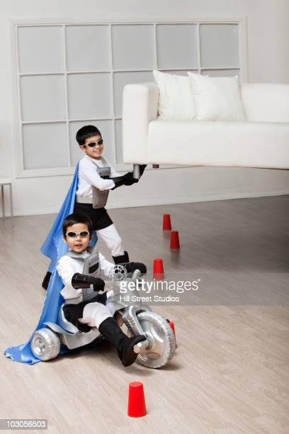 Korean superhero boy lifting sofa for brother to ride underneath
