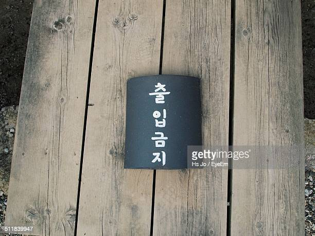 Korean text on black paper on wooden bench