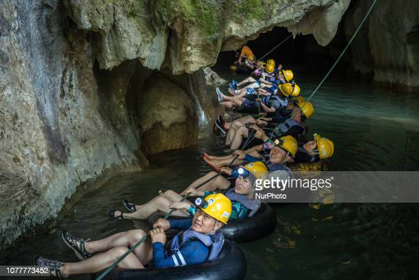 Korean tourists have a water cave tour in Vang Vieng Laos in December 2018 Since the end of the 90s Vang Vieng has been opened as a tourist site for...