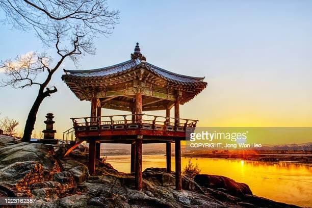 a korean traditional gazebo on the rock by the river in the morning sun - corée photos et images de collection
