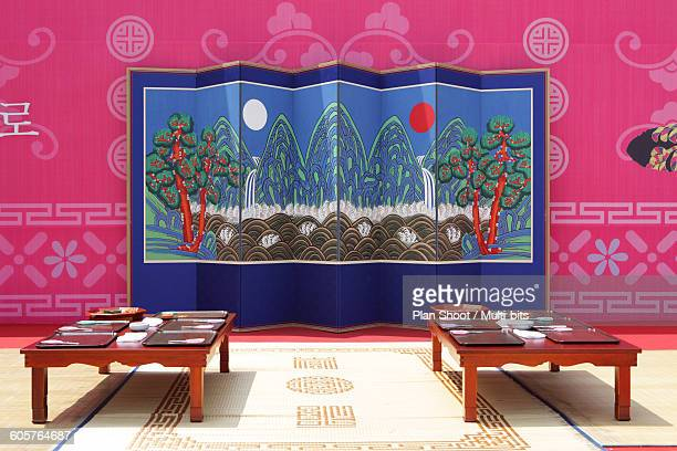 Korean traditional room with folding screen and tables