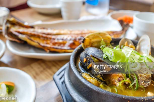 korean traditional seafood stew and fried mackerel at background - sungjin kim stock pictures, royalty-free photos & images