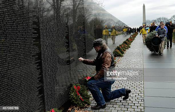 Korean War veteran Bill Leblander pays his respects to a fallen colleague at the Vietnam Veterans Memorial as a Christmas tree is carried to the apex...