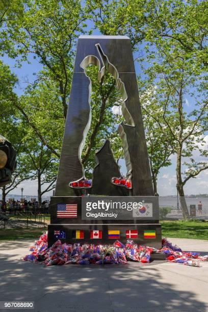 korean war veterans memorial, flowers, green trees and blue sky, battery park, new york city. - korean war memorial stock pictures, royalty-free photos & images